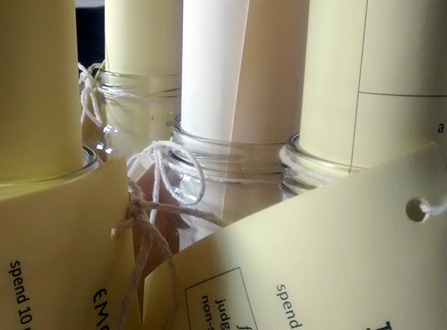 Handouts on pale yellow paper rolled and tucked into jars, with instructions tied on with string